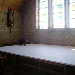 nettoyage de la toile blanche du lavement des pieds dans l'église de saint-tugdual